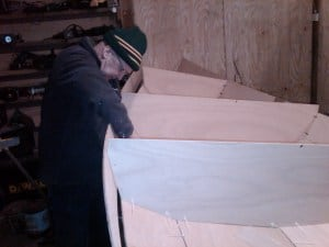 Canoe building. Seat support being stitched in place